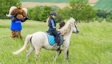 Mädchen beim Reiten mit Maskottchen Kasimir