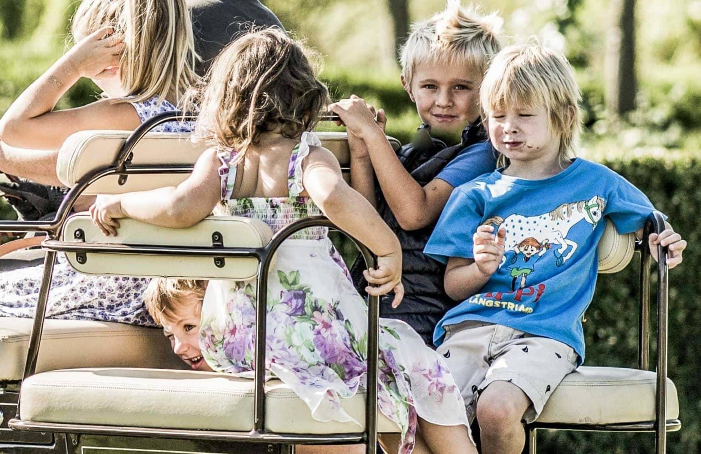Kinder fahren mit dem Golfcart mit