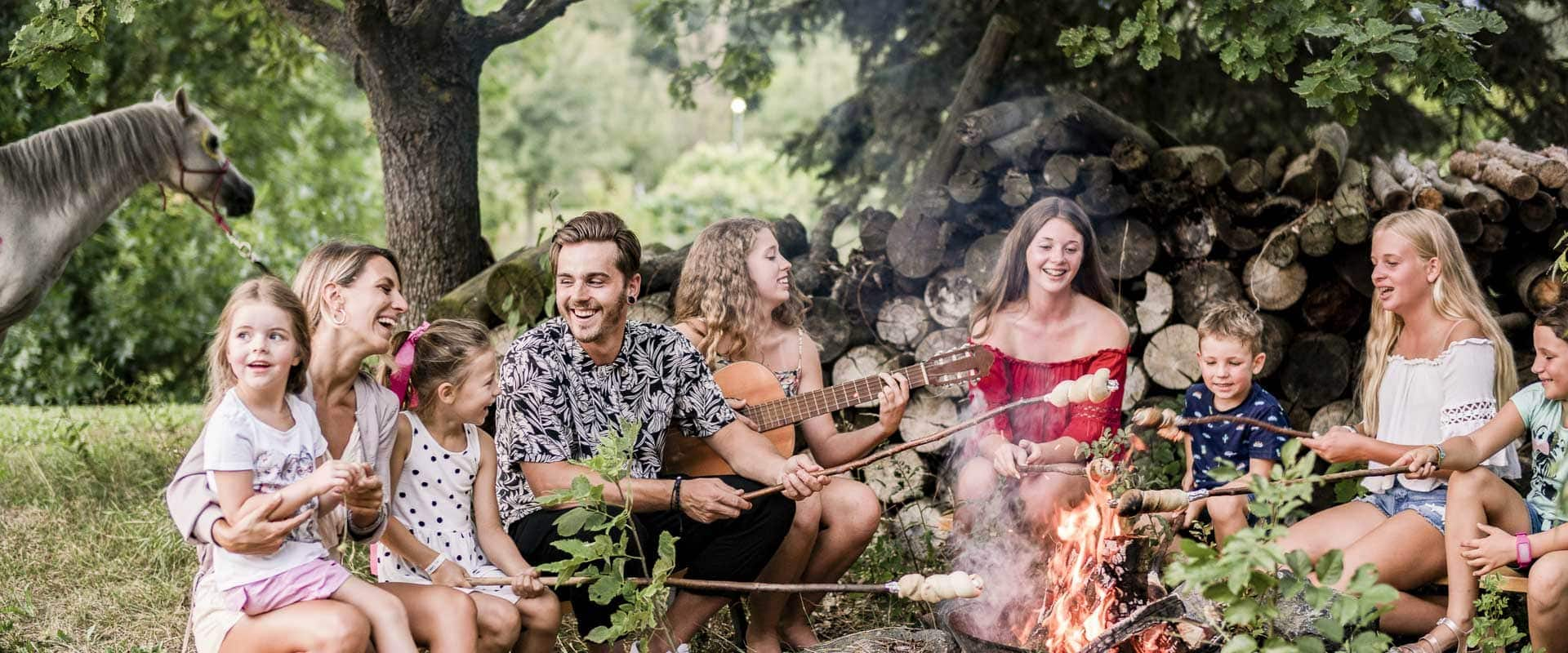 Kids sitzen ums Lagerfeuer mit Gitarrenbegleitung