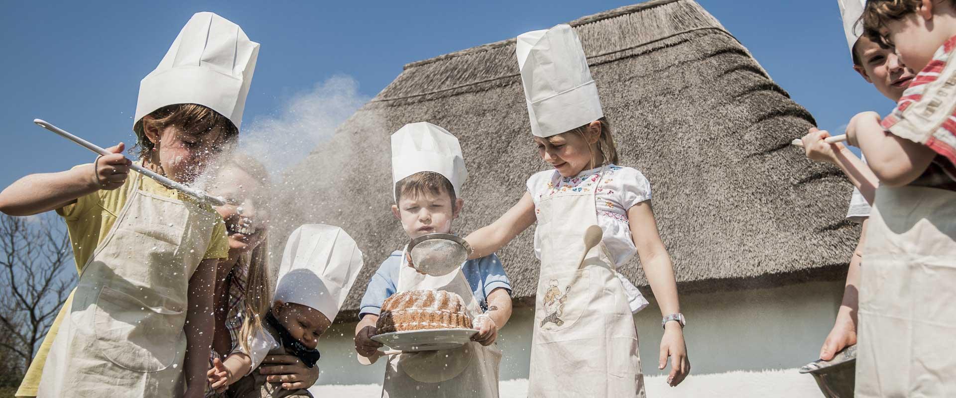 Kinder beim Dekorieren von selbstgebackenem Kuchen