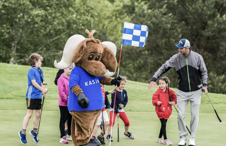 Kinder beim Golfspielen mit Maskottchen Kasimir