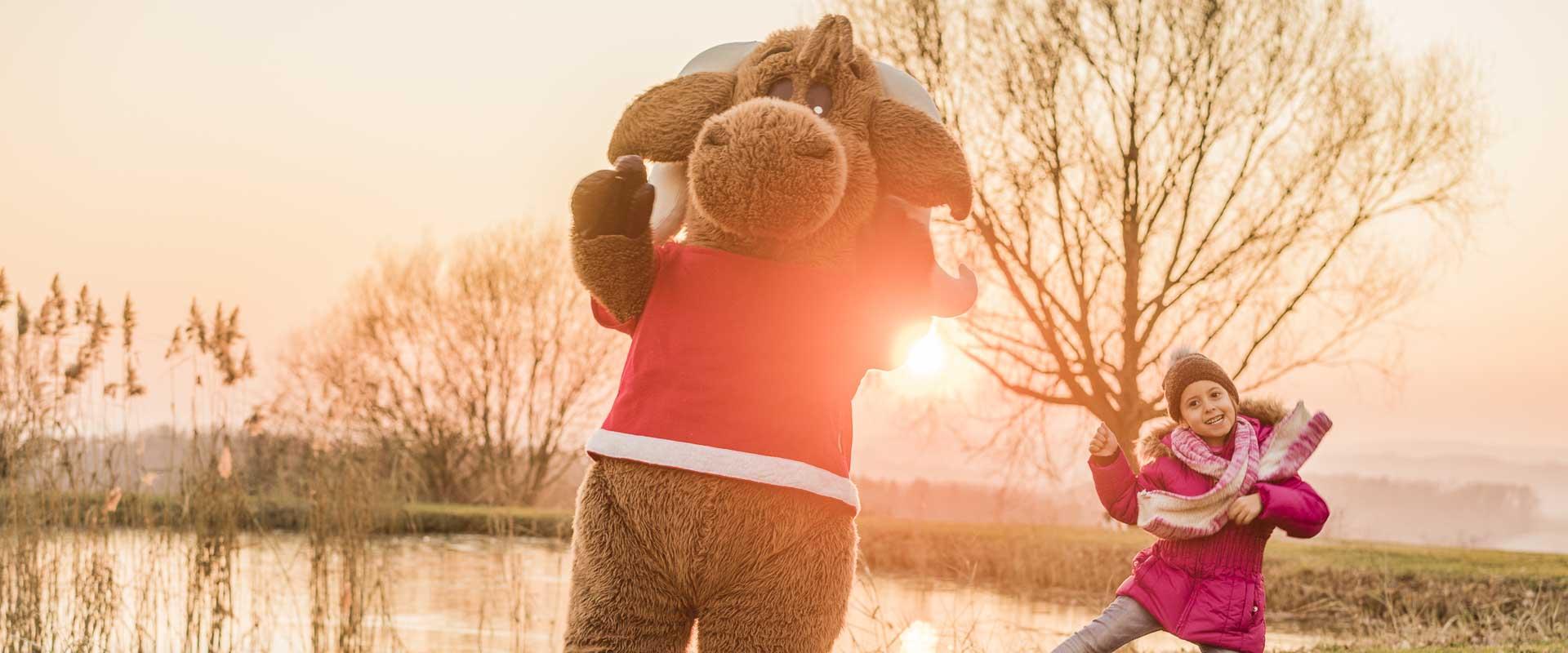Maskottchen Kasimir beim Tanzen mit einem Mädchen bei Sonnenuntergang