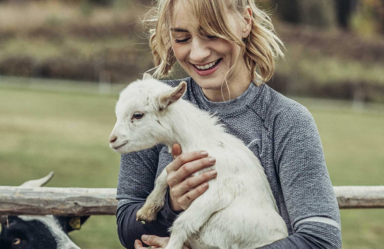 Frau beim Streicheln eines Ziegenbabies