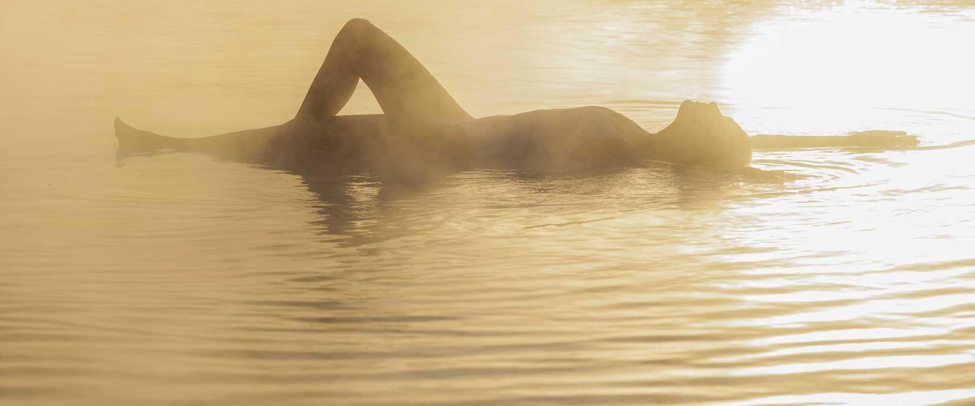 Frau in Pool bei Sonnenuntergang