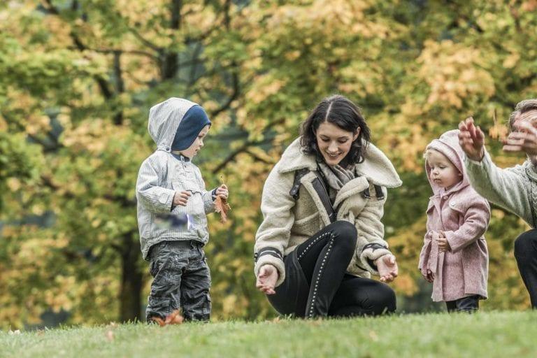 Familie beim Spielen mit Blättern im Herbst