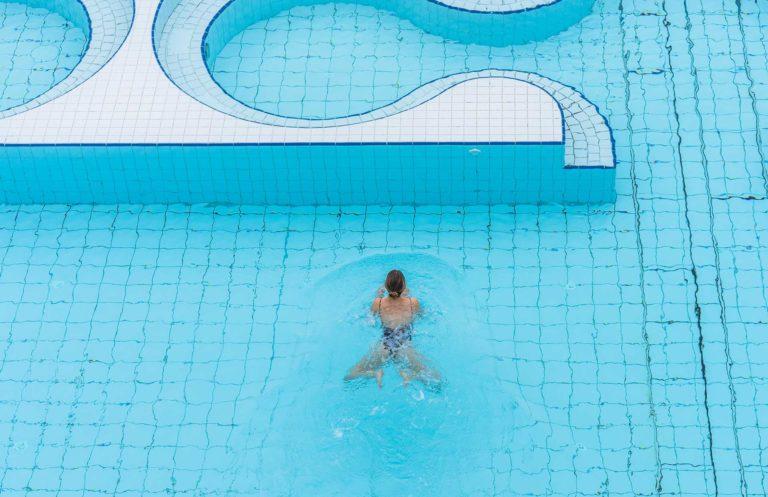 Frau schwimmt im Outdoorpool