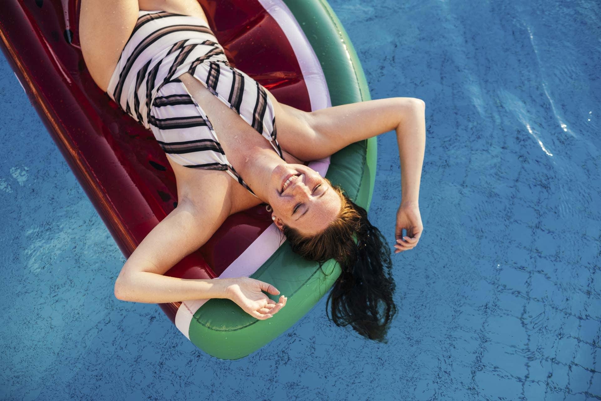 Frau auf Luftmatratze im Pool