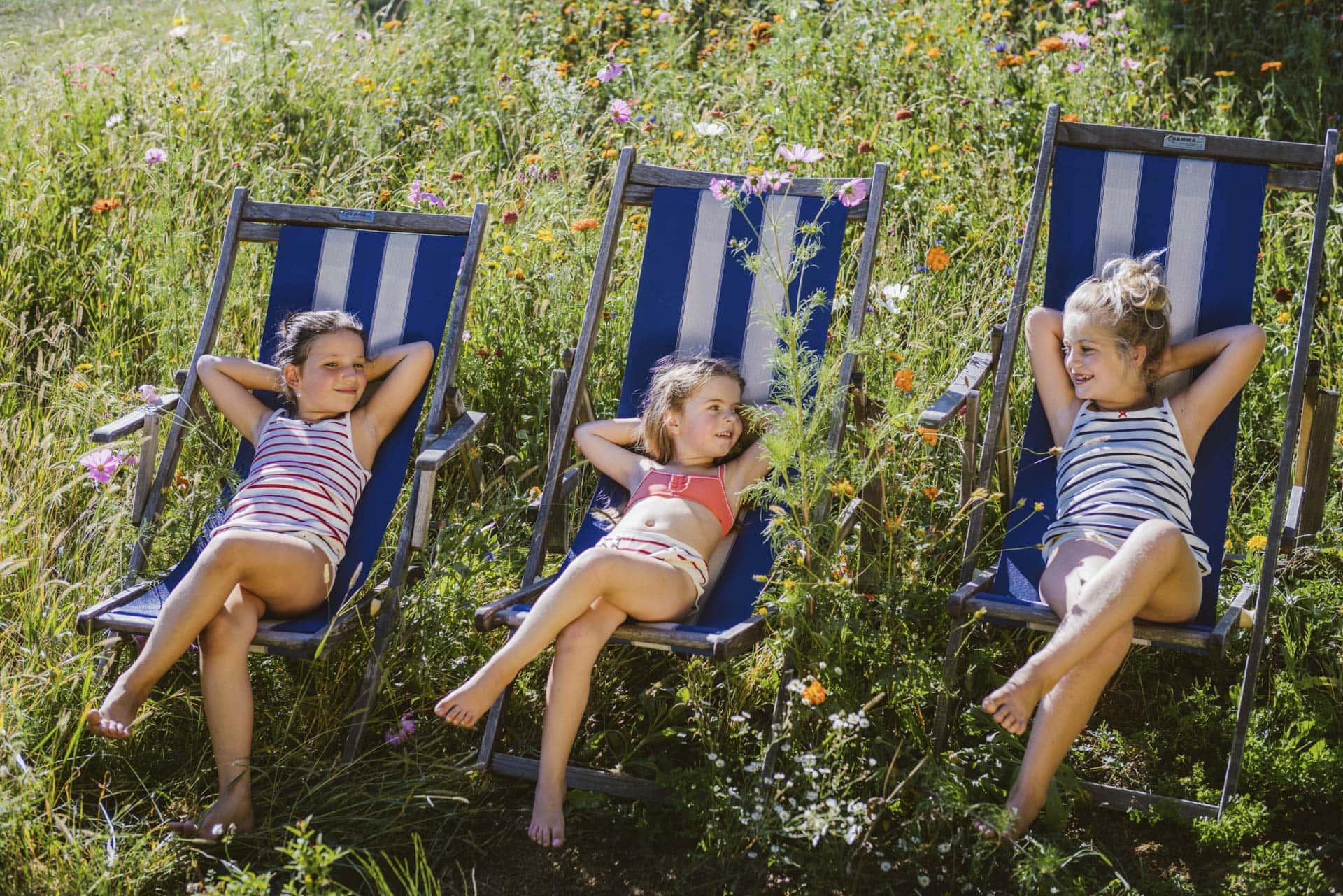 Mädchen auf Liegestuhl in einer Blumenwiese