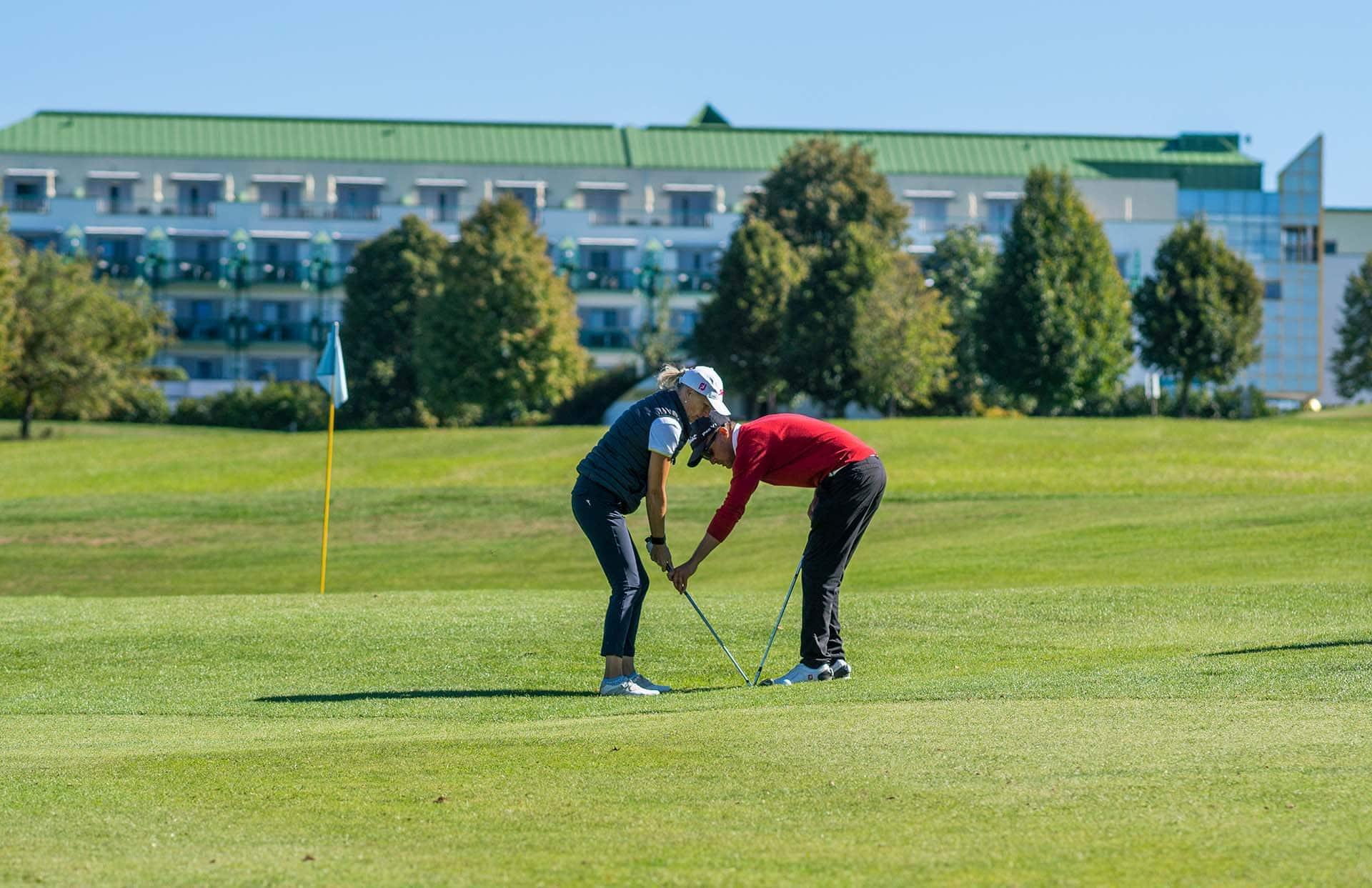 Frau mit Golftrainer am Golfplatz