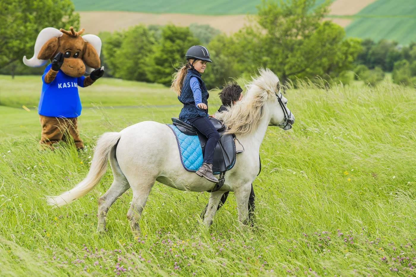 Mädchen reitet auf Pferd mit Maskottchen Kasimir im Hintergrund