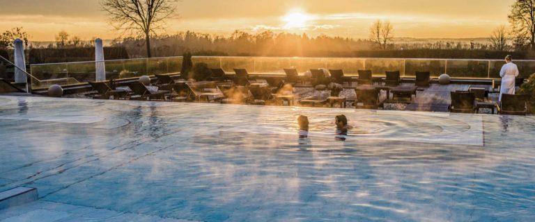 Paar badet im Oudoor-Pool bei Sonnenuntergang