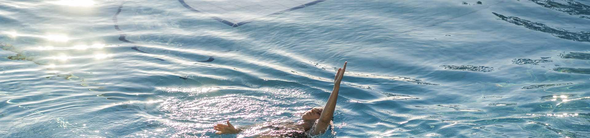Frau beim Rückenschwimmen im Pool