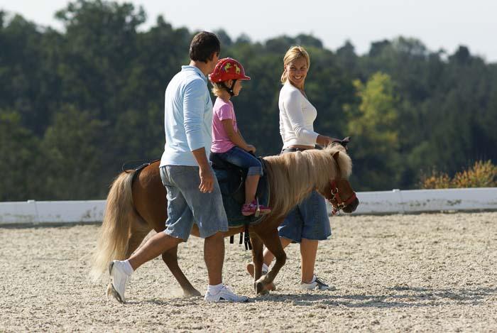 Familie mit Kind beim Ponyreiten