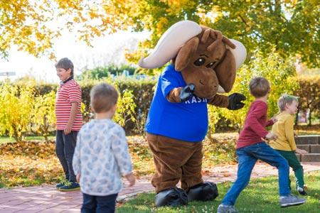 Maskottchen Kasimirs beim Spielen mit Kindern im Herbst