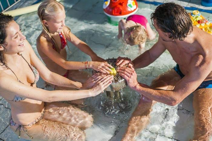 Familie mit Kindern beim Spielen im Wasser
