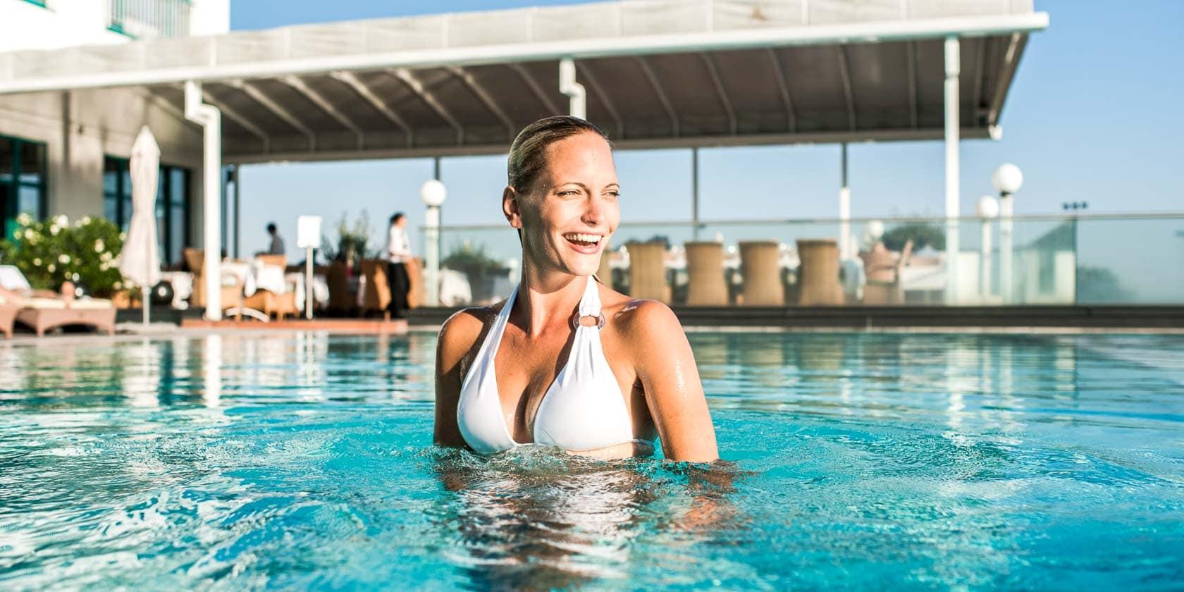 Frau lachend im Pool