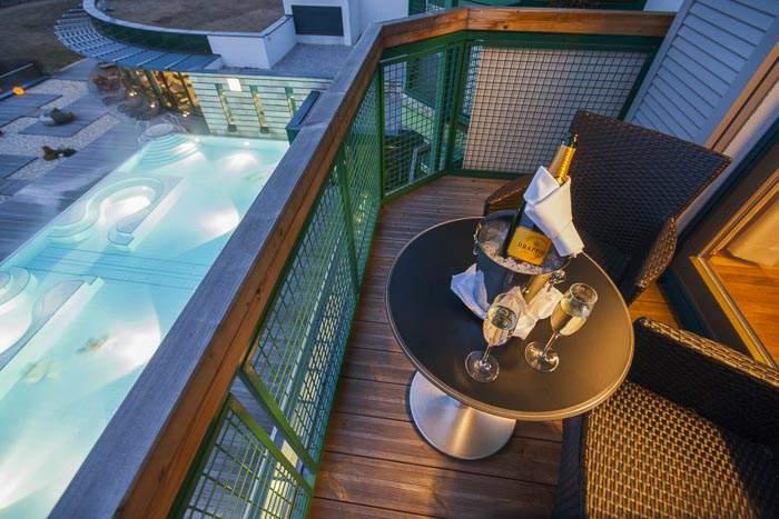 gekühlter Champagner auf Terasse mit Blick auf Pool