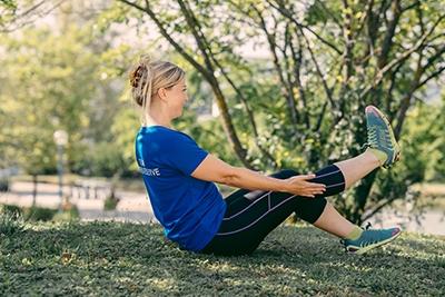 Frau macht Pilates Übungen im Freien